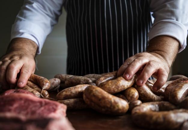 Un chef cuisinier préparant l'idée de recette de photographie de nourriture de saucisses