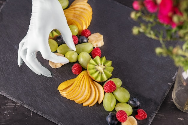Chef cuisinier prépare un dessert avec des fruits dans le restaurant.