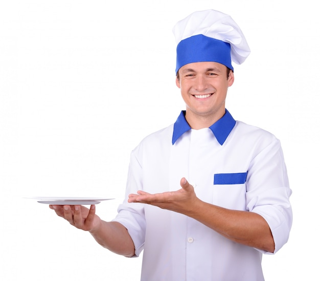 Chef cuisinier en uniforme remise assiette blanche, isolée sur blanc.