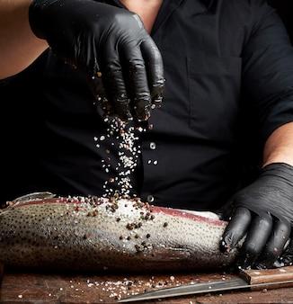 Le chef dans une chemise noire et des gants en latex noir prépare un filet de saumon sur une planche à découper en bois
