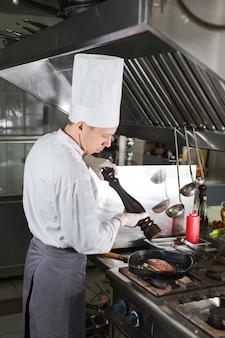 Chef dans la cuisine du restaurant au poêle avec poêle, cuisson