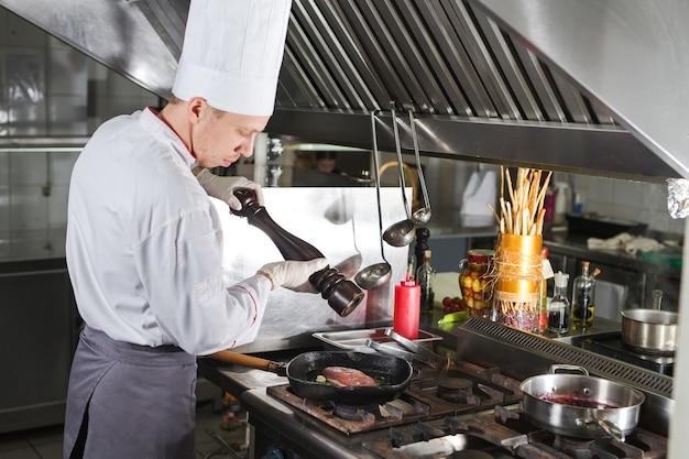 Chef dans la cuisine du restaurant à la cuisinière avec la casserole, la cuisine