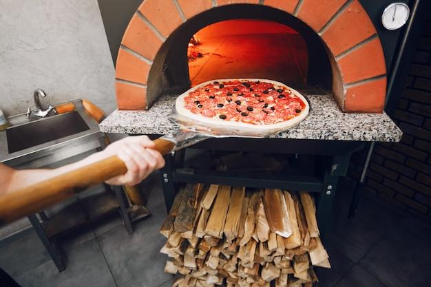Chef dans la cuisine prépare une pizza