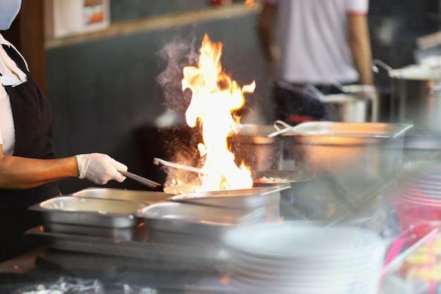 Le chef dans les gants en caoutchouc fait cuire au feu en gros plan