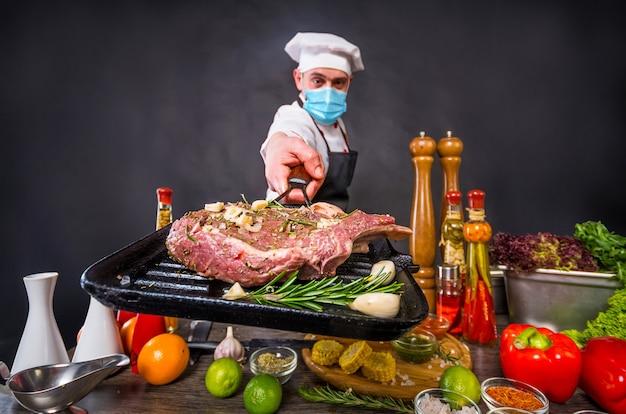 Chef dans un masque médical prévoyant de cuisiner un steak de boeuf tomahawk