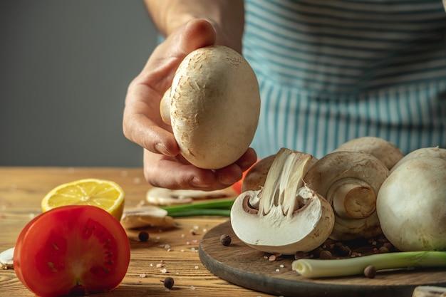 Le chef dans un tablier rayé bleu tient un champignon frais dans sa main au-dessus d'une table en bois avec des légumes et d'autres ingrédients pour faire cuire le plat