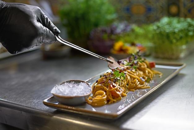 Chef décore des plats avec des tranches de truffe, gros plan