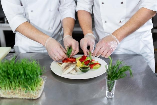 Le chef décore le poisson microgreens avec des légumes