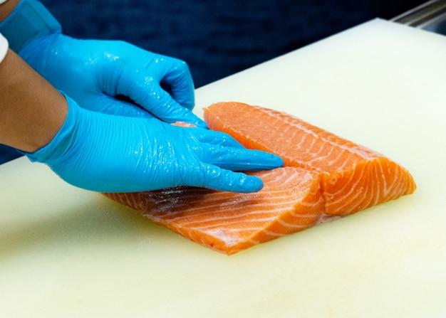Chef découpant du saumon frais cru, chef préparant un saumon frais sur une planche à découper