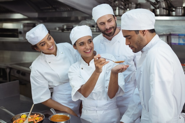 Chef dégustation de nourriture à un collègue dans la cuisine