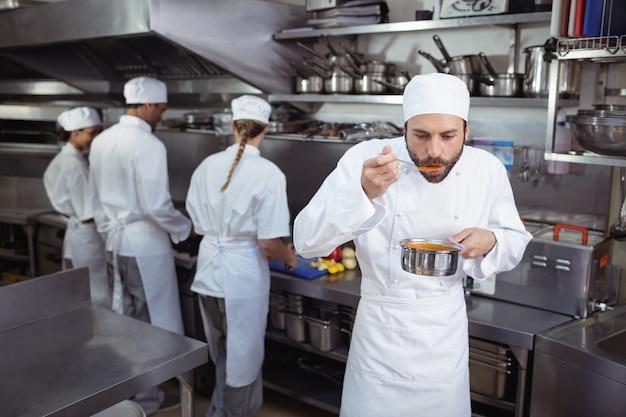 Chef, dégustation de nourriture de cuillère dans la cuisine