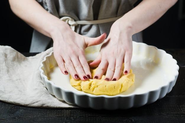 Le chef déroule la pâte dans un plat allant au four, en cuisinant