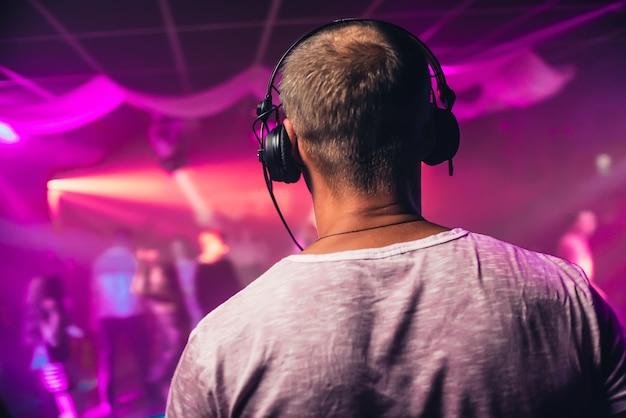 Chef de dj avec un casque jouant lors d'un événement en discothèque avec un éclairage lumineux