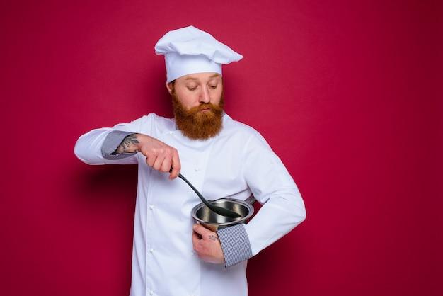 Le chef douteux avec barbe et tablier rouge est prêt à cuisiner