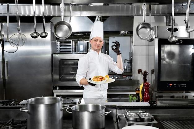 Le chef du restaurant tient une assiette avec un plat préparé et montre le signe