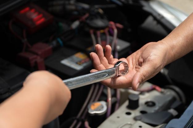 Le chef du technicien du service de réparation de moteur de voiture donne une clé au collègue