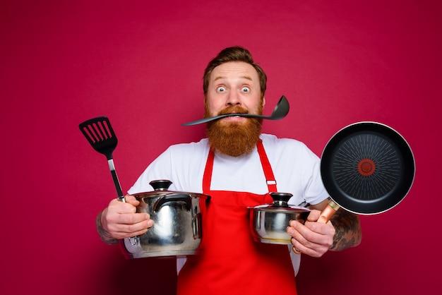 Le chef effrayé avec la barbe et le tablier rouge est prêt à cuisiner
