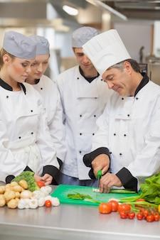 Chef enseignant la coupe de légumes à trois stagiaires