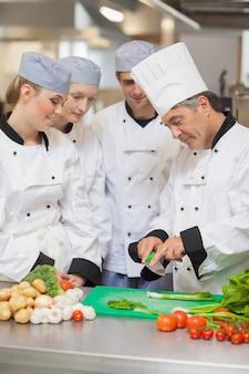 Chef enseigner aux stagiaires comment couper les légumes