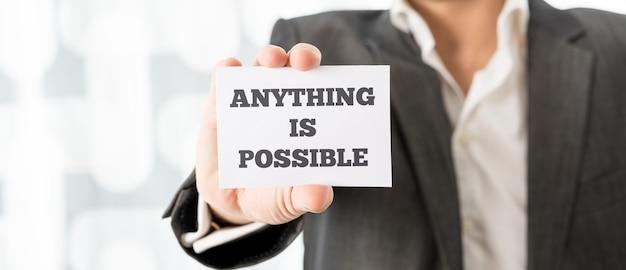 Chef d'entreprise brandissant une carte blanche avec tout est possible signe afin de motiver son équipe