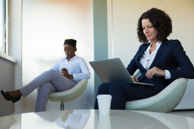 Chef d'entreprise confiant travaillant sur ordinateur dans un salon de bureau