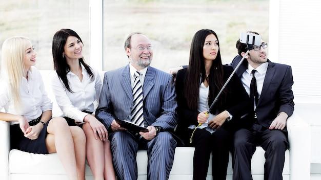 Chef d'entreprise et fonctionnaires subordonnés souriants faisant selfie au bureau.
