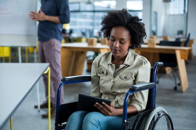 Chef d'entreprise handicapé en fauteuil roulant à l'aide de tablette numérique