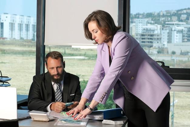 Chef d'entreprise payant de l'argent en espèces en shekels ils à un employé de bureau