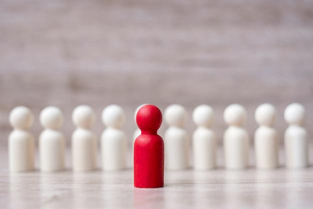 Chef d'entreprise rouge avec une foule d'hommes en bois. leadership, affaires, équipe, travail d'équipe et gestion des ressources humaines