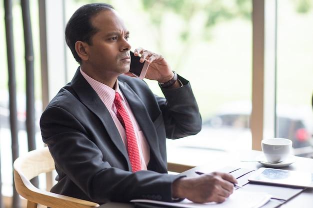 Chef d'entreprise sérieux appelant au téléphone au café