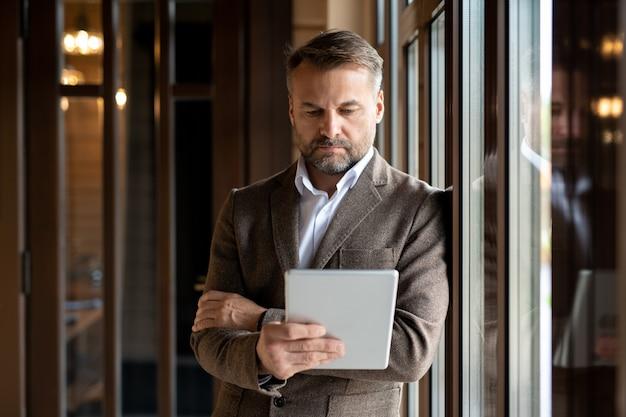 Chef d'entreprise sérieux dans les vêtements de cérémonie se concentrant sur le réseau tout en regardant l'écran tactile en position debout par fenêtre