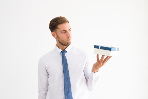 Chef d'entreprise sérieux tenant une boîte cadeau avec noeud de ruban