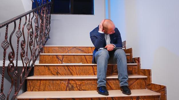 Chef d'entreprise travaillant tard dans la nuit, finissant le projet d'échéance de l'entreprise, fermant l'ordinateur portable et vérifiant les documents du presse-papiers assis dans les escaliers du bâtiment de l'entreprise.