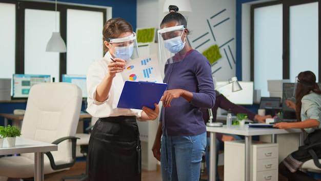 Chef d'entreprise avec visière contre le coronavirus expliquant à un collègue africain le plan de projet debout devant le bureau tenant le presse-papiers. équipe commerciale multiethnique travaillant dans le respect de la distance sociale.