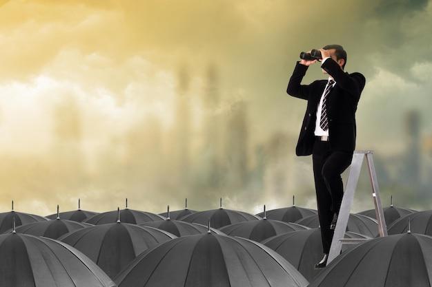 Chef d'entreprise de vision utilisant des jumelles pour regarder et trouver des opportunités sur la stratégie normale du parapluie noir.