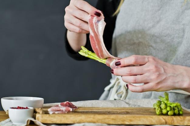 Chef enveloppé dans des mini asperges au bacon. vue de côté, cuisine, concept de cuisson des asperges au bacon.