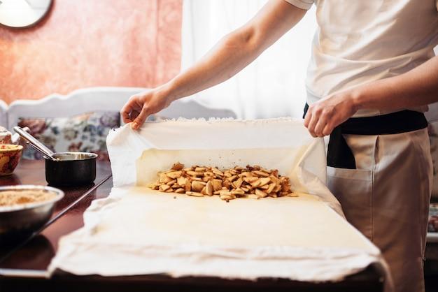 Le chef enveloppe la garniture dans une pâte, un strudel aux pommes