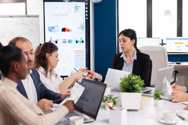 Chef d'équipe de start-up donnant des tâches à des collègues multiethniques