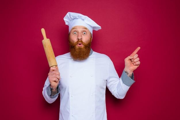 Le chef étonné avec la barbe et le chef de tablier rouge tient le rouleau à pâtisserie en bois