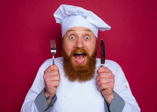 Le chef étonné avec la barbe et le tablier rouge tient des couverts à disposition