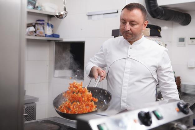 Chef expérimenté faisant frire des légumes dans la cuisine du restaurant, espace de copie