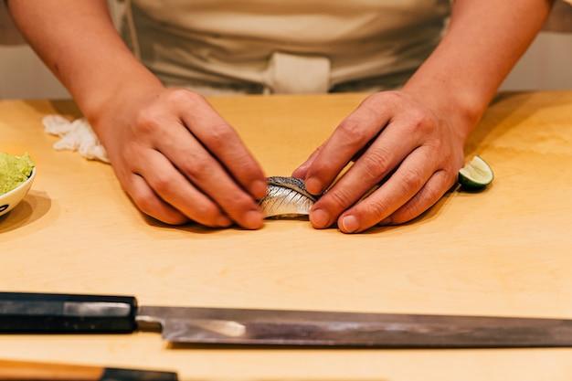 Chef faisant le menu omakase: saba sushi (maquereau) à la main sur le comptoir de la cuisine en bois. repas de luxe japonais.