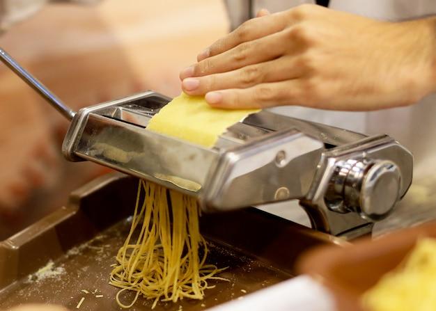 Chef faisant des pâtes avec une machine, des pâtes fraîches faites maison