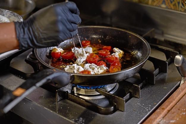 Le chef fait frire dans une casserole les tomates et les huîtres, prépare le plat dans la cuisine.