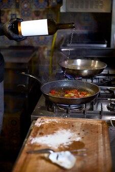 Le chef fait frire le vin blanc dans une casserole les tomates et les huîtres,