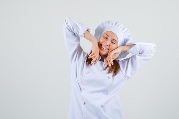 Chef féminin étirement des bras en uniforme blanc et à la détente