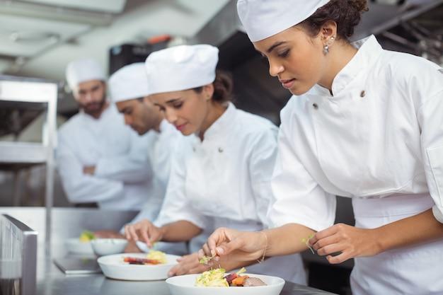 Chef féminin garnir la nourriture dans la cuisine