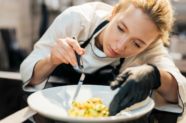 Chef féminin mettant de la nourriture sur une assiette