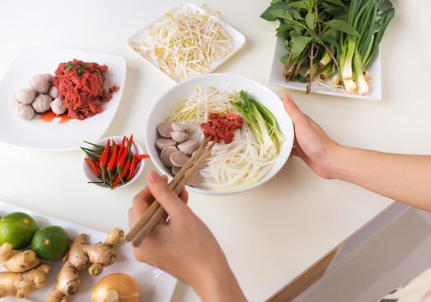 Chef féminin préparer la soupe traditionnelle vietnamienne pho bo avec des herbes, de la viande, des nouilles de riz