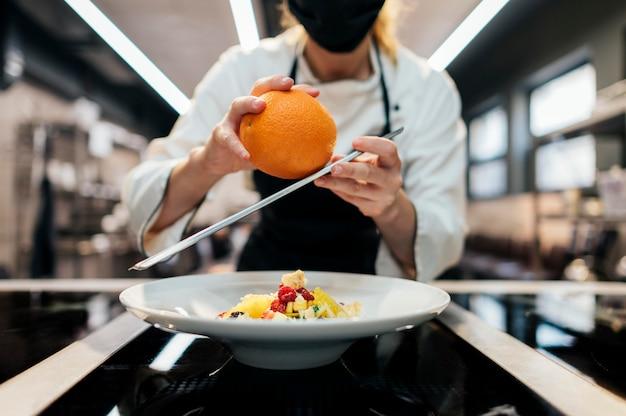 Chef féminin râpant la peau d'orange sur le plat